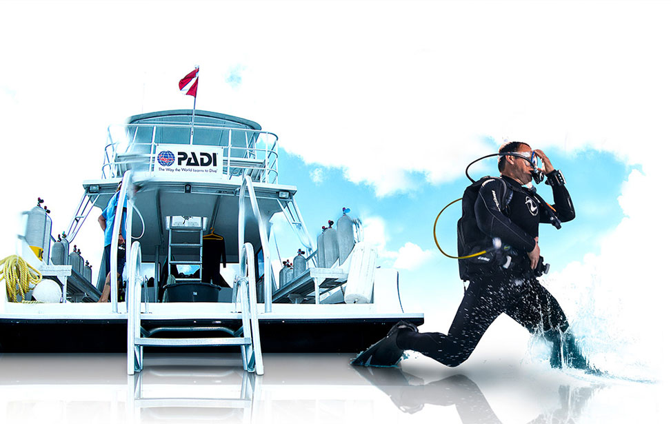 Divers entering the water from a PADI boat